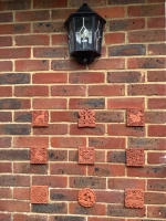 Collection of tiles lovingly displayed on patio wall in Bexhill-on-Sea (UK)