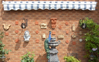 Collection of tiles lovingly displayed on wall in Carlton Colville (UK)